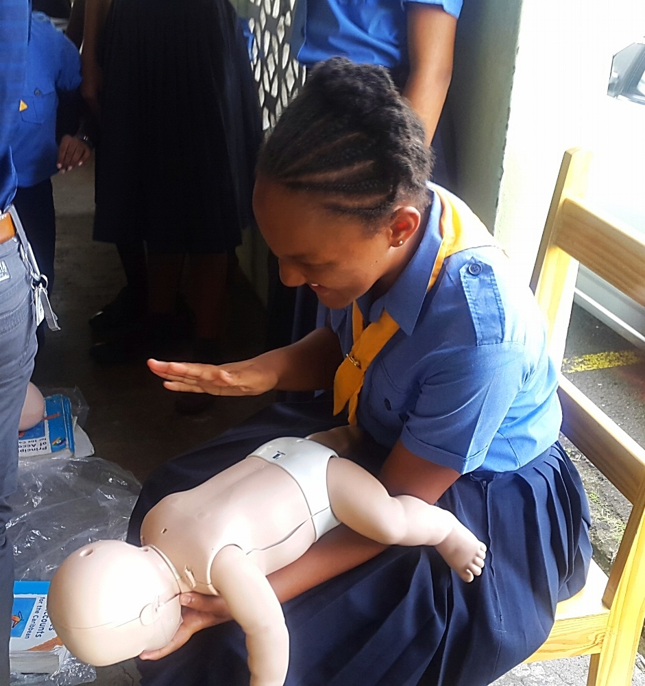 A Girl Guide learning how to aid a choking infant