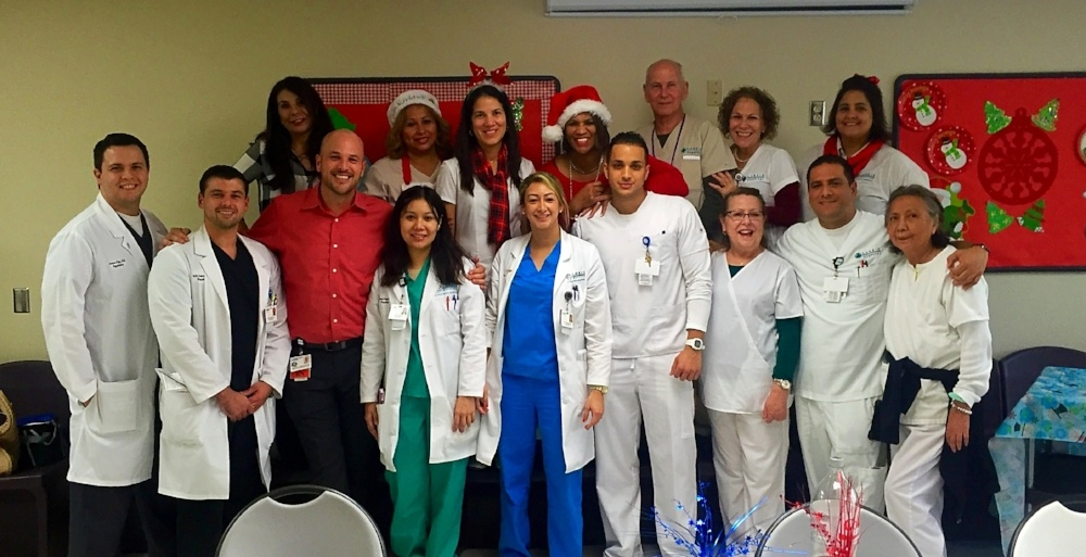 Trinity graduate Dr. Hernandez (center) at a holiday work event